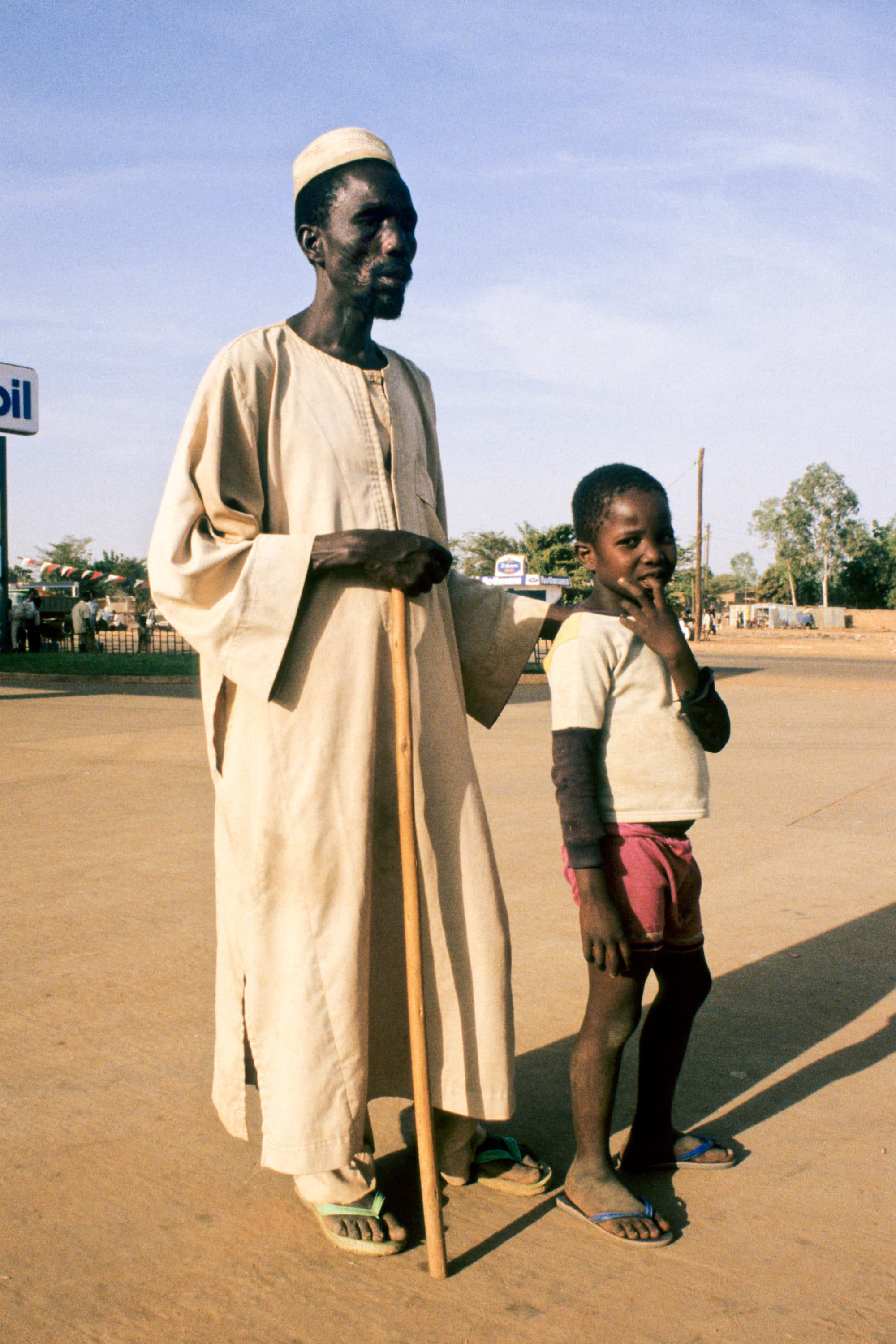 Nigerian man effected by blindness, being led by his son.