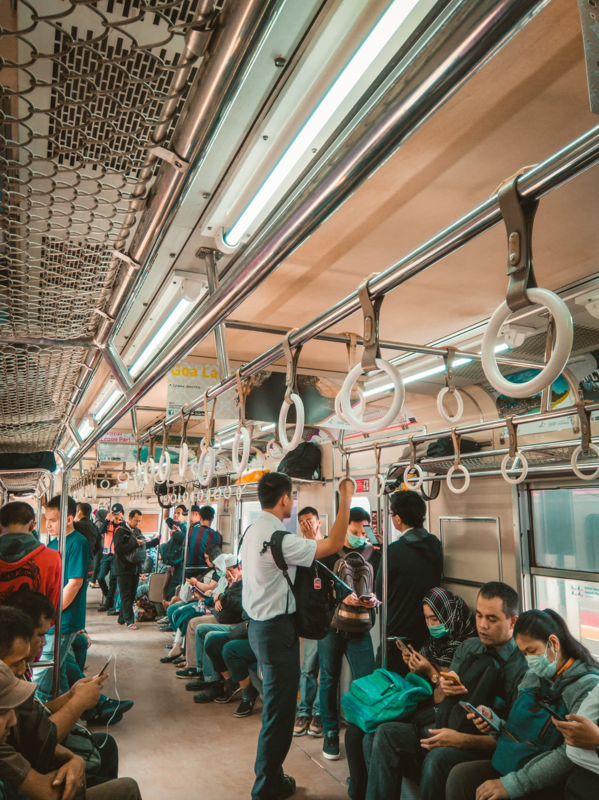 Interior of a relatively full Indonesian subway or train car.