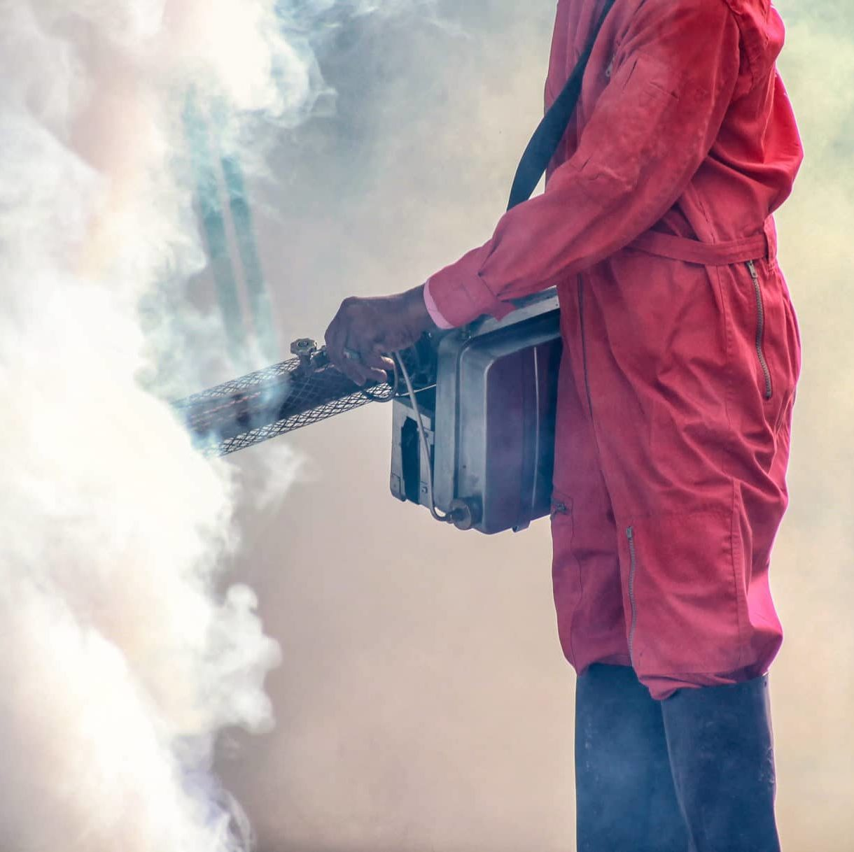 Man in red protective gear, fumigating.