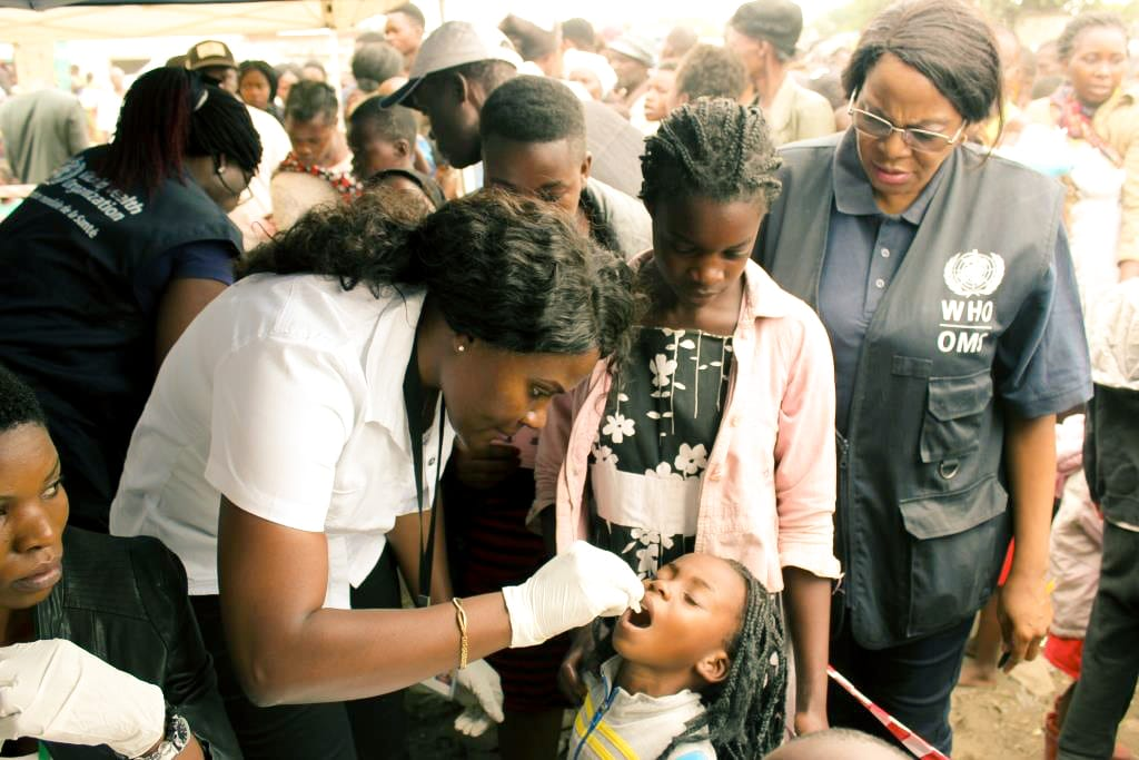 A woman administering a vaccination to a young girl among a crowd.