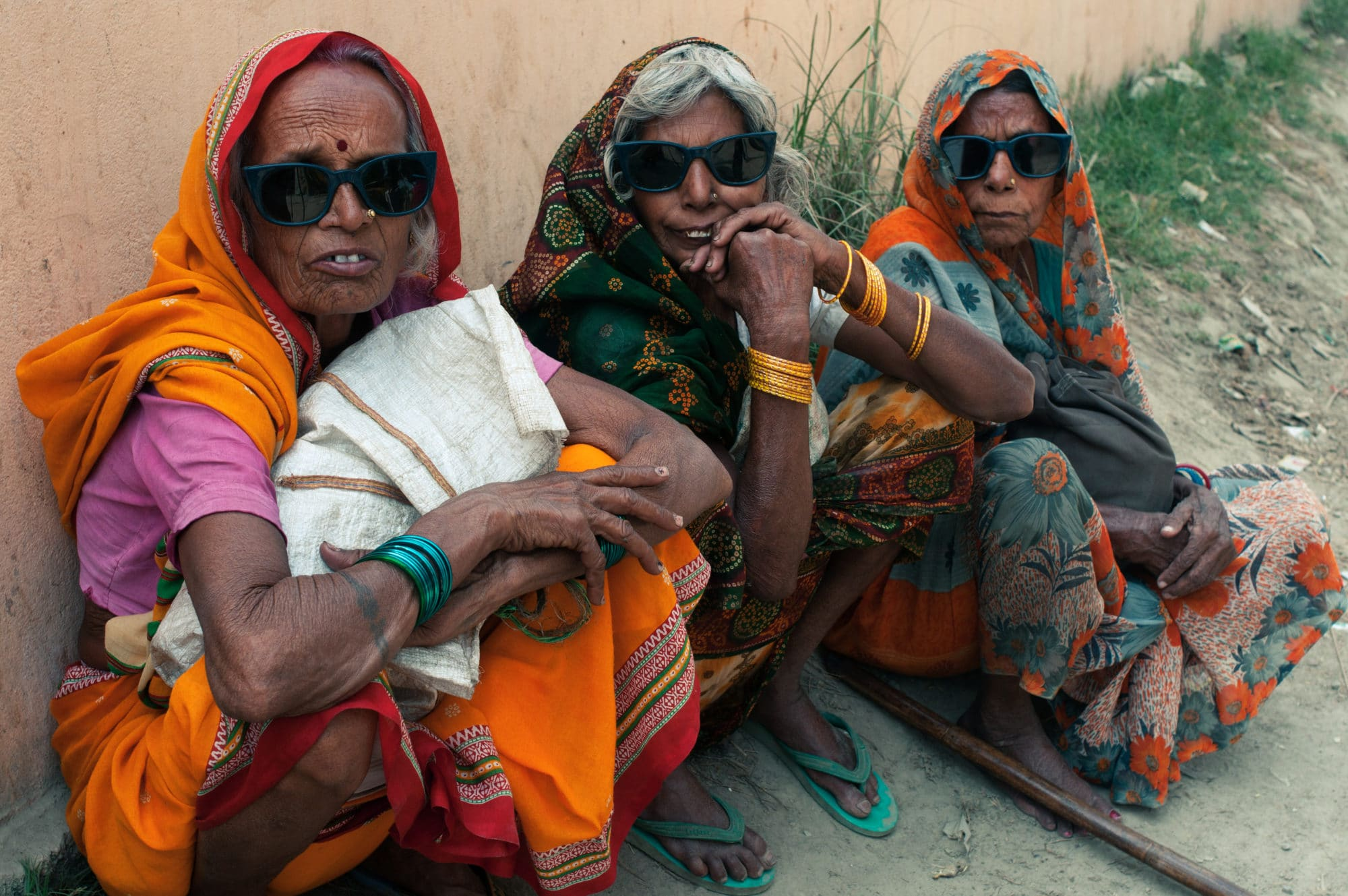 Three Indian cataract patients sit next to a building, all wearing matching protective sunglasses.